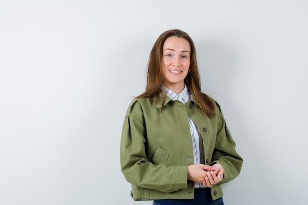 Giovane donna che guarda l'obbiettivo in camicia, giacca e guardando allegro, vista frontale.