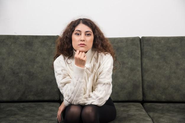 Giovane donna che guarda la telecamera e si siede sul divano