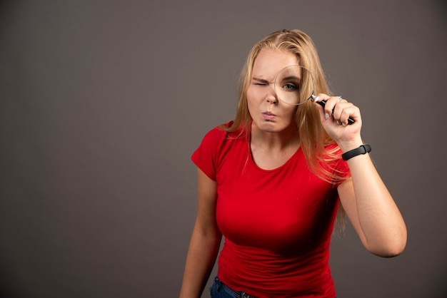 Young woman looking at camera through magnifying glass.