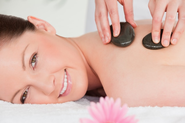 Young woman looking at the camera while having a stone massage