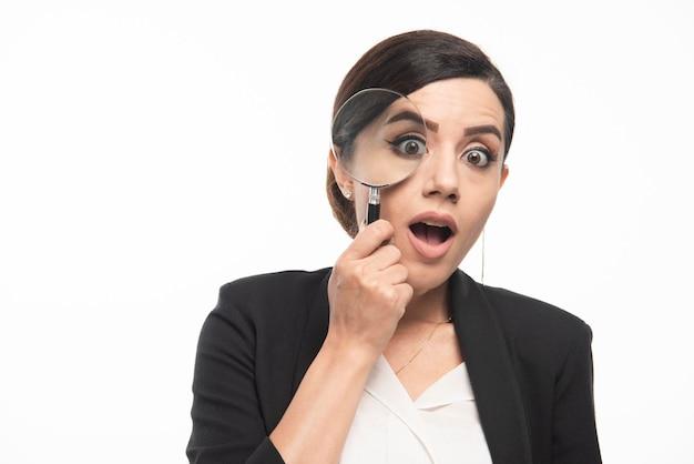 Giovane donna che guarda l'obbiettivo con lente d'ingrandimento. foto di alta qualità