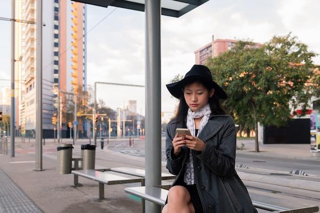 Молодая женщина смотрит мобильный телефон в ожидании автобуса