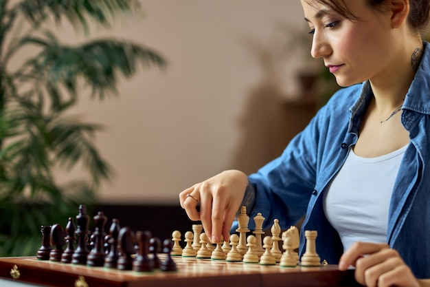 Young woman looking at the chess pieces on the board and making move while playing chess board game