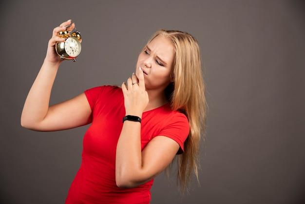 Giovane donna che guarda l'orologio con espressione stanca.