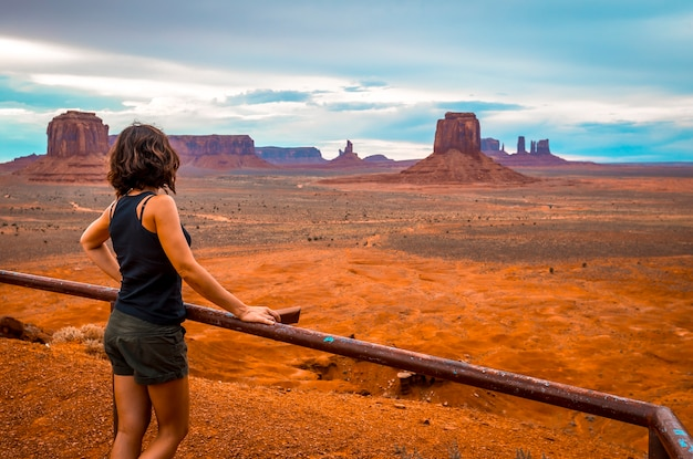 A young woman looking in a cloudy monument valley national park.