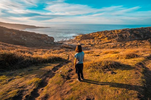 A young woman looking at the coast of mount jaizkibel near san sebastian, gipuzkoa. spain