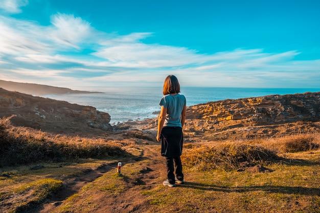 A young woman looking at the coast and the sea of the jaizkibel mountain near san sebastian, gipuzkoa. spain