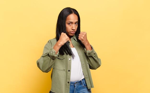 自信を持って、怒って、強くて攻撃的に見える若い女性で、ボクシングの位置で戦う準備ができている拳を持っている