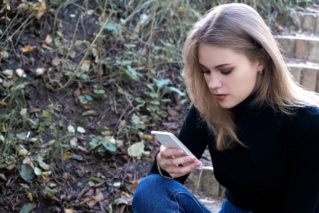 公園の電話、テキストメッセージ、アプリケーションの使用に不満を感じている若い女性