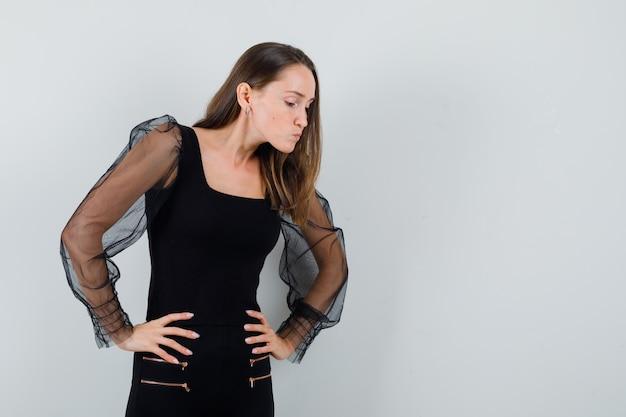 검은 블라우스에 신중 하 게 내려다보고 초점을 맞춘 젊은 여자. 전면보기. 텍스트를위한 공간