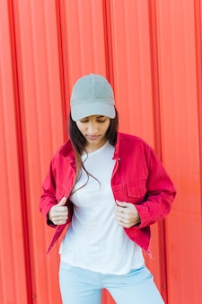 Young woman looking down while holding red jacket standing against metal backdrop