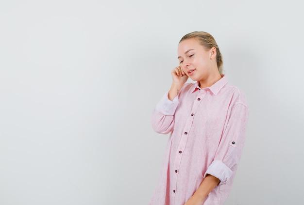 Молодая женщина смотрит вниз, думая в розовой рубашке и смотрит с надеждой