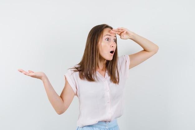 Молодая женщина смотрит вдаль с раскинутой ладонью в футболке, юбке и выглядит изумленным. передний план.