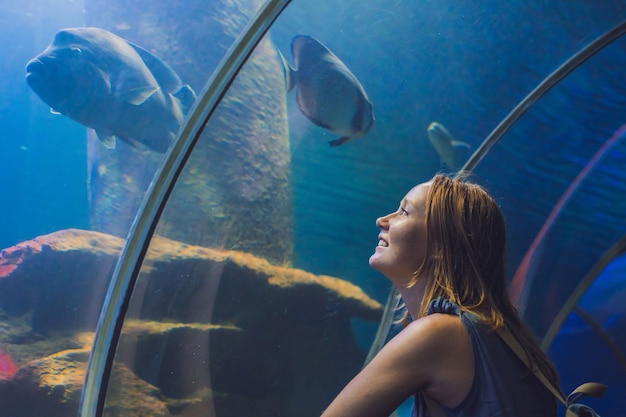 Young woman looking at fish in a tunnel aquarium.