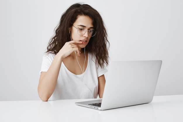 Young woman looking focused on project in laptop, working at office