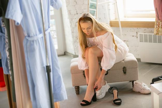 Молодая женщина ищет новую одежду