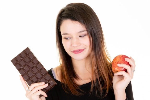 Young woman looking fresh apple while eating chocolate bar