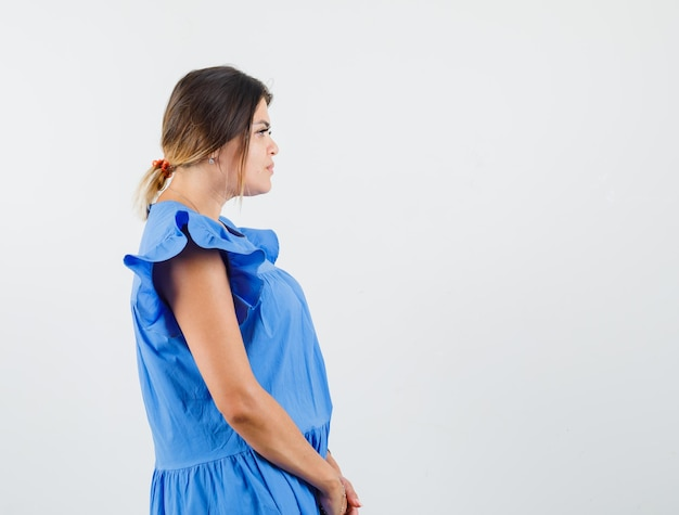 Young woman looking at front of her in blue dress and looking focused