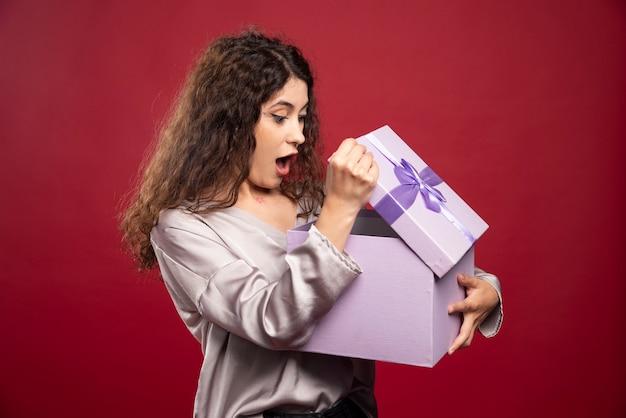 Giovane donna che esamina il contenitore di regalo e ottenere sorpreso.