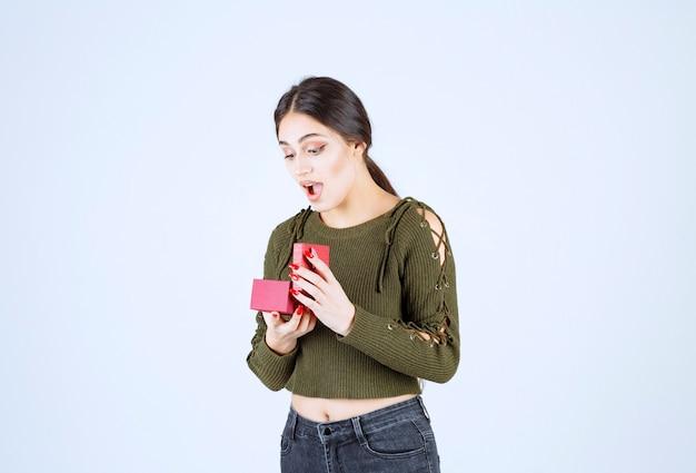 Giovane donna guardando confezione regalo su sfondo bianco.