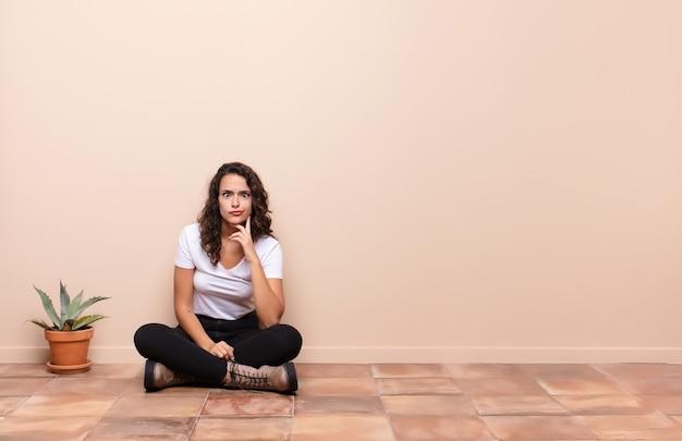 Молодая женщина выглядит глупо и смешно с глупым косоглазым выражением лица, шутит и дурачится, сидя на полу террасы