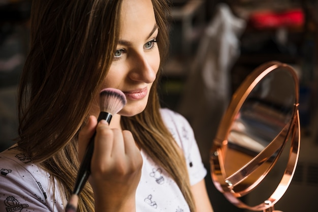 Young woman looking at hand mirror doing makeup