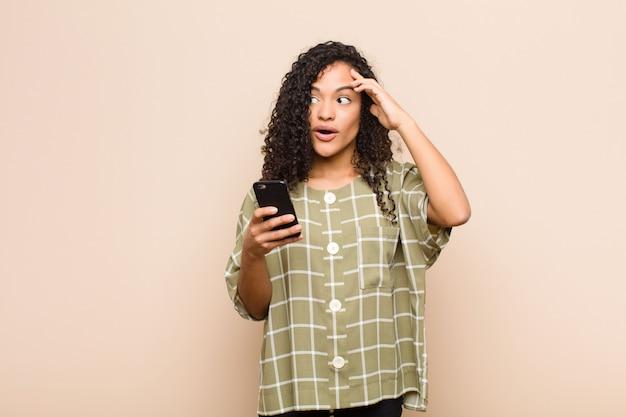 幸せそうに見える若い女性、驚いた、驚いた、笑みを浮かべて、スマートフォンで素晴らしいと信じられないほどの良いニュースを実現