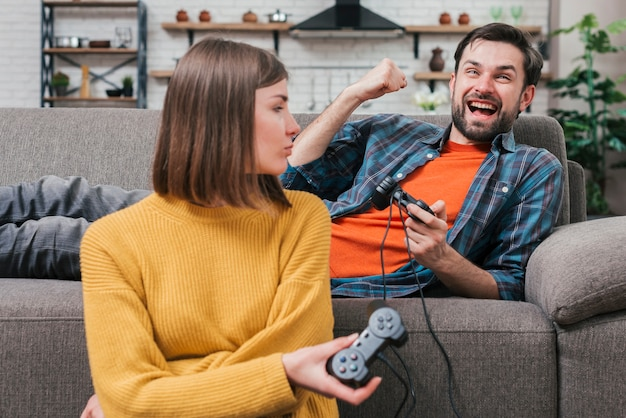 Young woman looking at her boyfriend lying on sofa cheering after winning the video game