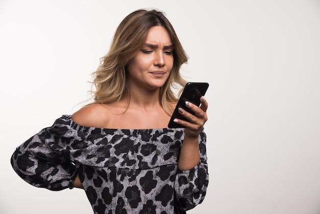 Молодая женщина, глядя на свой телефон на белой стене.