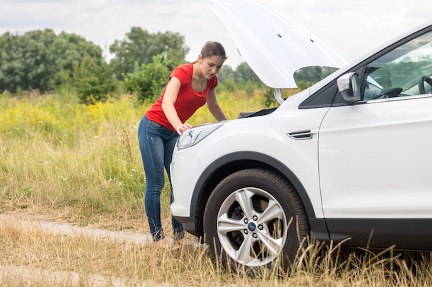 Young woman looking under the hood of overheated car at meadow