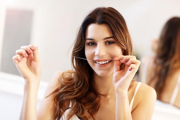 Молодая женщина смотрит в зеркало в ванной
