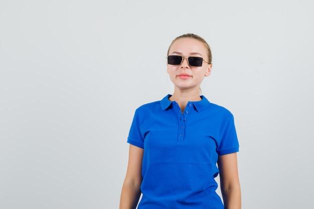 Молодая женщина смотрит в синюю футболку, очки и уверенно