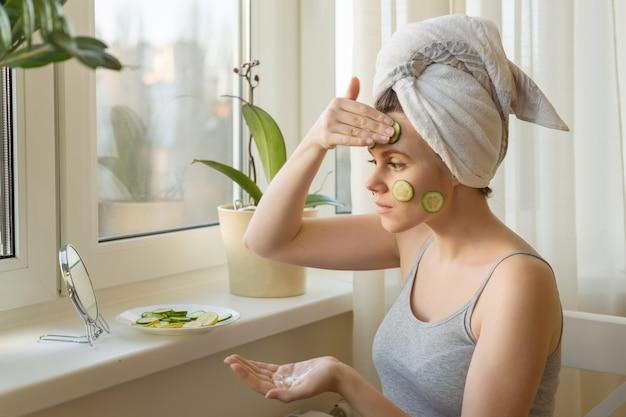 젊은 여자가 거울을보고 크림으로 얼굴을 돌보고 마스크 만들기