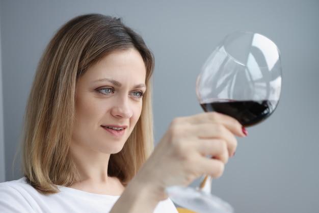 레드 와인으로 유리를 찾는 젊은 여자