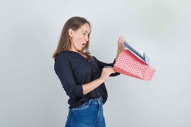 黒のシャツ、ジーンズのショートパンツで紙袋を見て、驚いて見える若い女性。 。