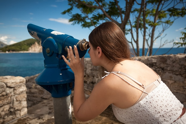 Young woman looking on landscape through touristic coin operated telescope