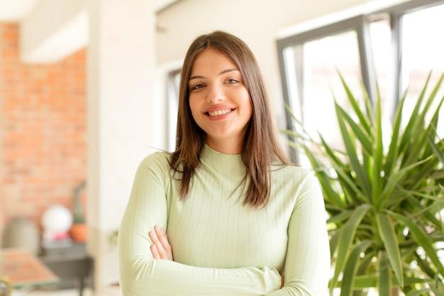 腕を組んで微笑んで幸せな誇りと満足の達成者のように見える若い女性