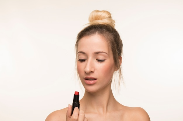 Young woman looking at lipstick