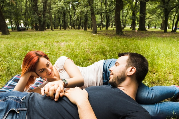 Young woman looking at man sleeping in the park