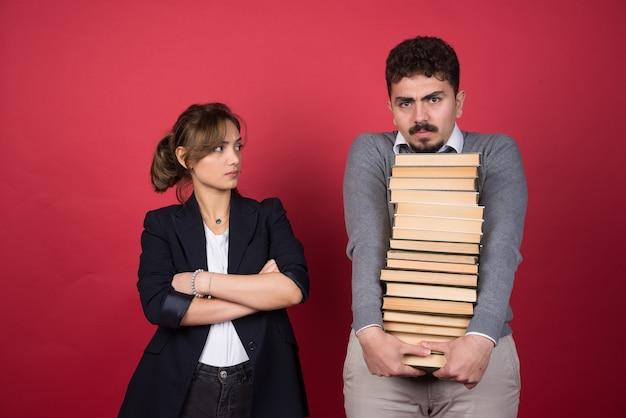 Giovane donna che guarda l'uomo che porta un mucchio di libri