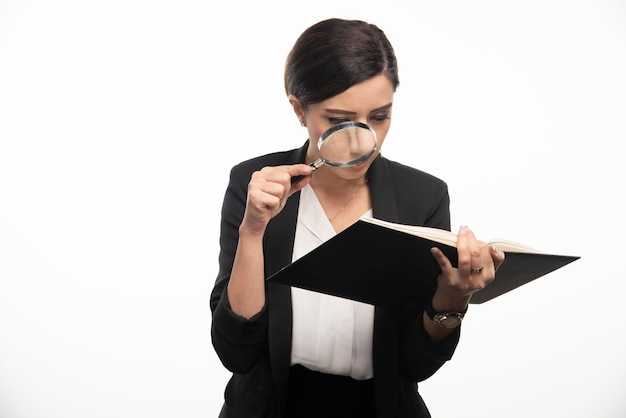 Giovane donna che esamina il taccuino con la lente d'ingrandimento. foto di alta qualità