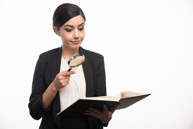 Young woman looking at notebook with magnifying glass. high quality photo