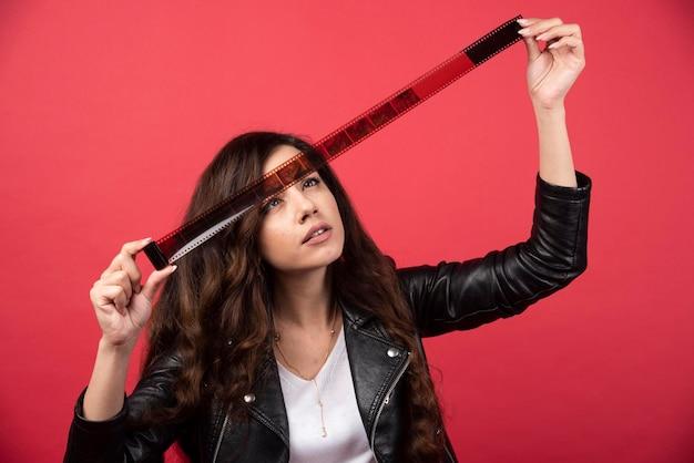 赤い背景に写真テープを見ている若い女性。高品質の写真 無料写真