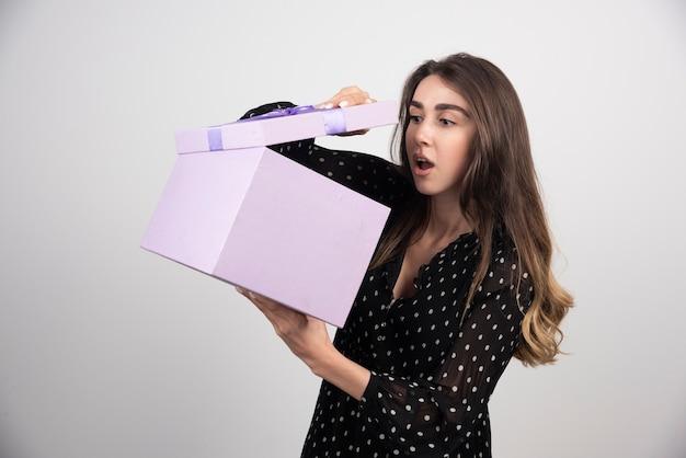 보라색 선물 상자에 찾고 젊은 여자