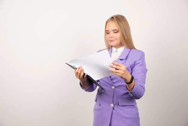 白のタブレットを探している若い女性。