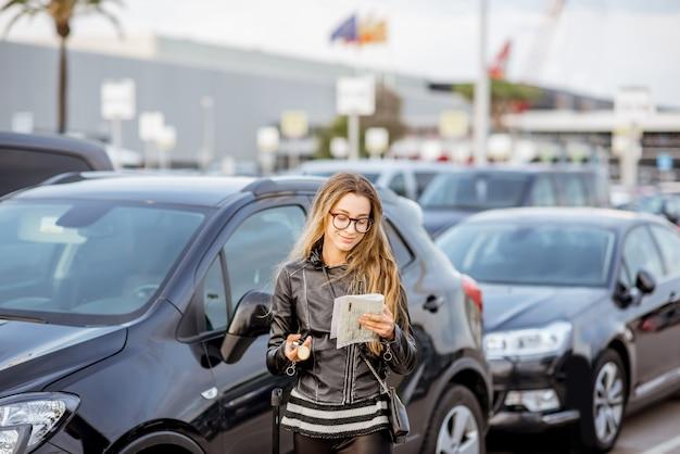공항 주차장에 야외에 서 있는 임대 계약서를 보고 있는 젊은 여성