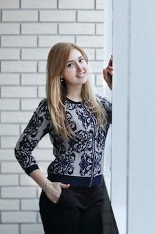 Молодая женщина, глядя в окно офиса. фотография с копией пространства