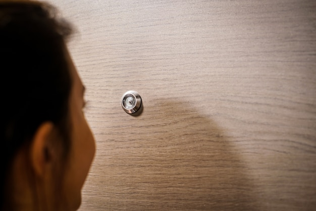 Young woman looking out through the peephole of her front door.