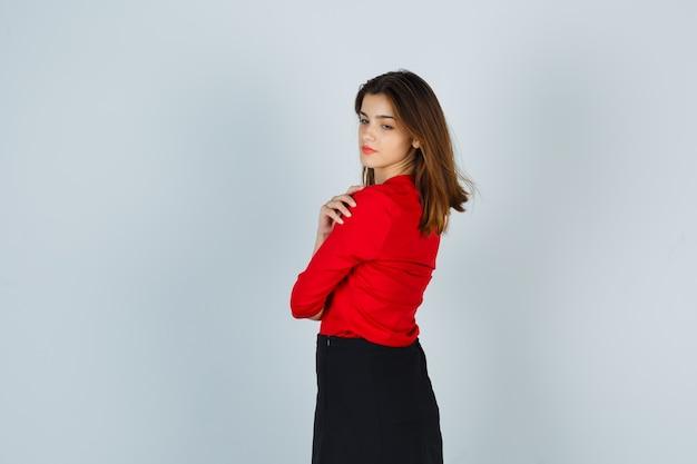 빨간 블라우스, 검은 치마에 어깨 너머로보고 예쁜 젊은 여자