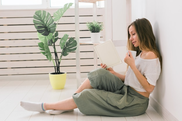 Молодая женщина смотрит фотоальбом дома и пьет чай воспоминания и концепция досуга